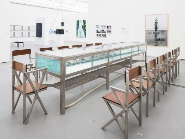 Klaus Rinke, Freitagessen, 1987, Wassertisch (ohne Karpfen), 13 verschieden konstruierte Stühle, Lichtuhr   © Photo by Reinhard Haider