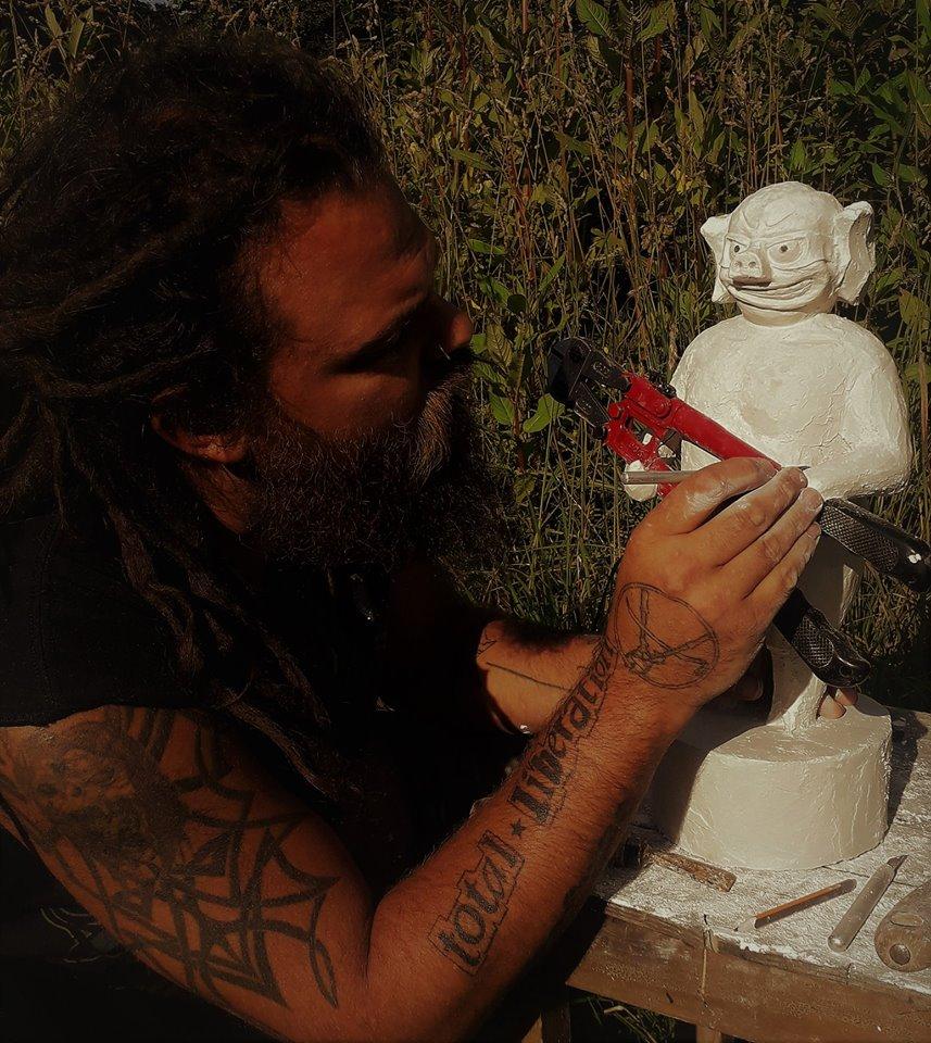 Chris Moser beim Anfertigen des Gipsmodells für den Bronzeguss. Am rechten Unterarm trägt er seine Forderung in die Haut tätowiert.